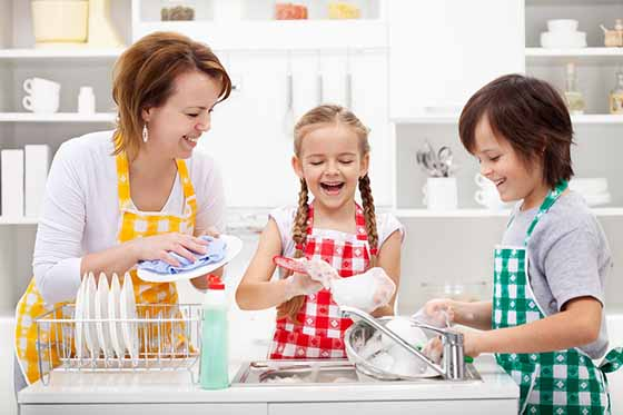 Kids and mother washing dishes - having fun together in the kitc