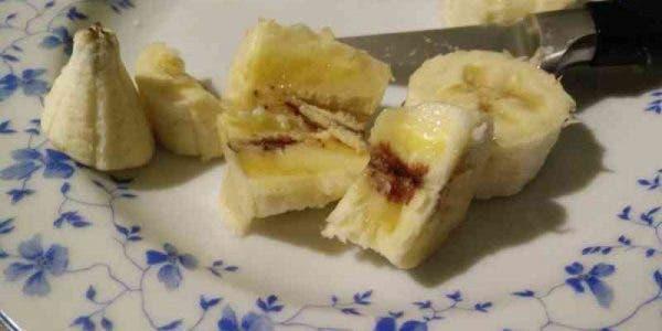 Un enfant mange une banane et remarque des lignes rouges à l'intérieur