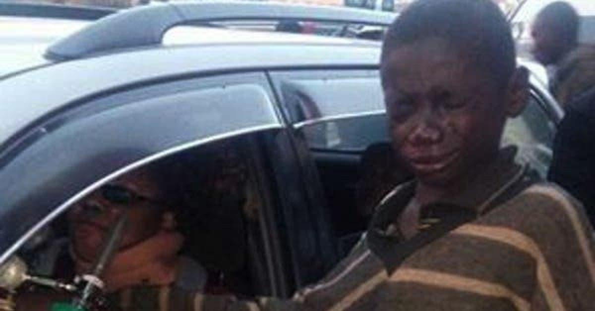 Un garçon s'approche d'une voiture pour demander de l'argent