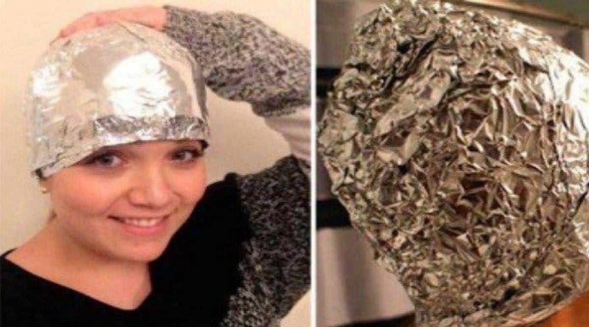 Une femme met du papier aluminium sur ses cheveux