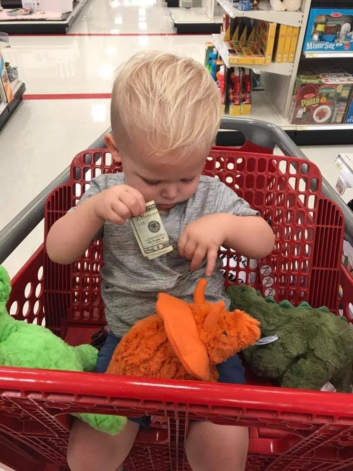 Une maman laisse un homme jouer avec son enfant dans un magasin