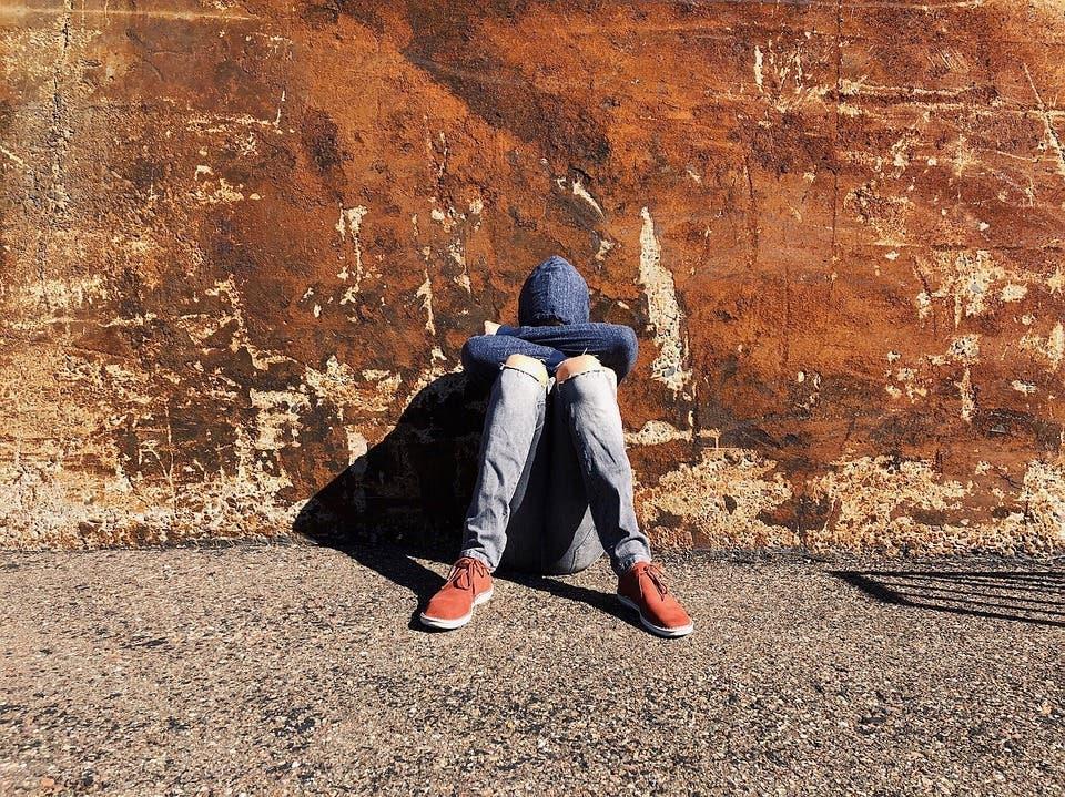 jeune homme assis dos au mur