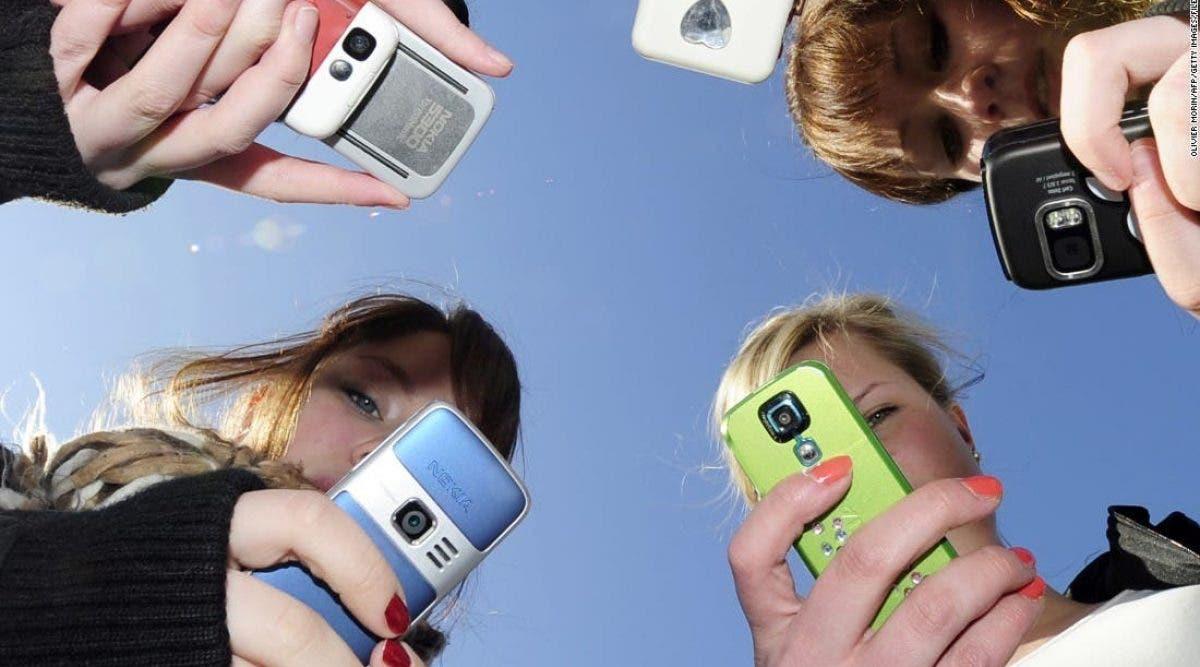 adolescents s'arrêtent pour regarder et filmer avec leur téléphone un jeune garçon en train de mourir