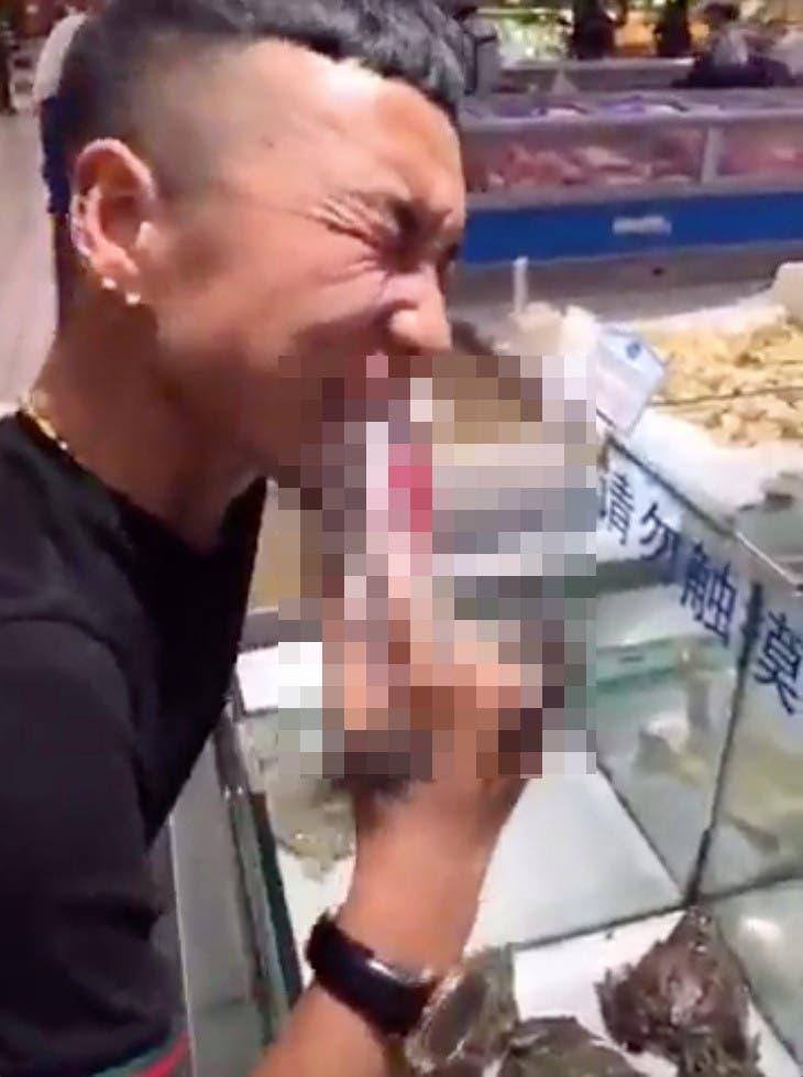 Un homme mange la tête d'une grenouille